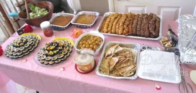 Savory table - kabob, sushi, pita bread, hummus, fish ball curry, huge container of basmati rice (covered in foil)
